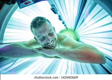 Man in sunbed relaxing and enjoying while getting a tan