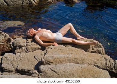A man sunburns on reefs at sea. Summer, sunny day.