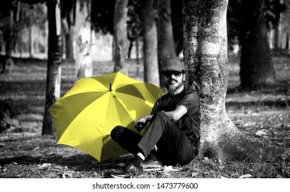 Man in a sunglass sitting beside a yellow umbrella