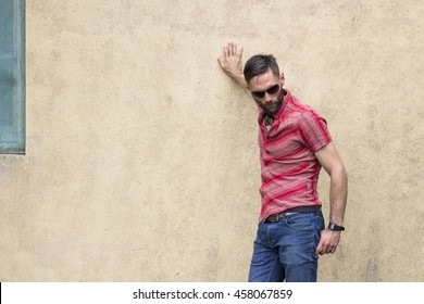 Man with sunglasses and beard leaning against the wall of an old house and looking down.