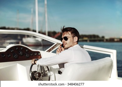 Man in sunglasses driving a yacht and talking on the phone