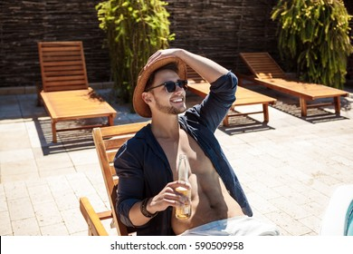 Man in sunglasses and hat drinking beer, sitting on chaise.