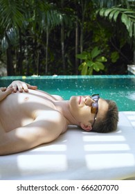 Man with sunglasses lying down by the pool