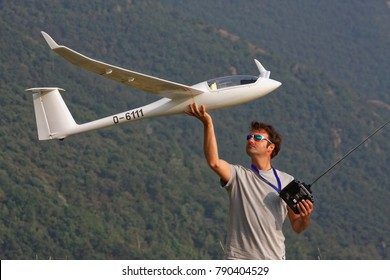 Man in sunglasses is playing with a ero plane glider discus 2c model with remote control in the top of a mountain