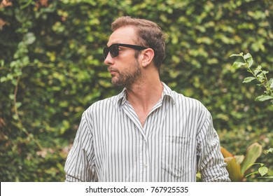 Man with sunglasses and shirt posing outdoors.