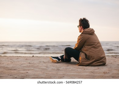 Man in sunglasses sitting near the ocean on the sunset