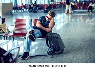 Man with sunglasses sleeping while sitting in airport terminal and waiting for flight departure