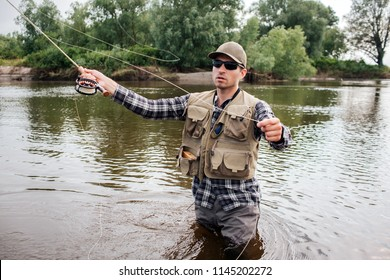 Man in sunglasses stands in water and fishing. He is preparing fly-fishing. Guy holds it in one hand and spoon in the other one. Man wears shirt, waders, vest and cap.
