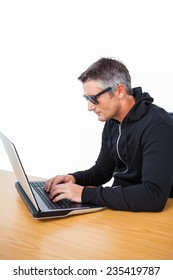 Man with sunglasses typing on laptop on white background