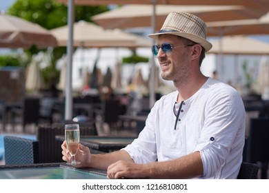 Man in sunhat and sunglasses is sitting at the pool bar in the hotel, smiling and holding a glass of sparkling wine. He is celebrating an event.