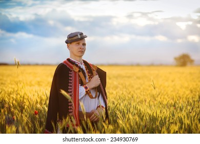 Man in the sunset field. He is wearing traditional Eastern Europe folk costumes.