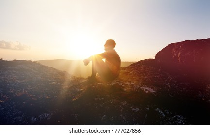 Man at sunset mountains
