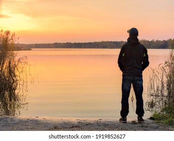 man and sunset next to lake in autumn