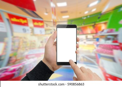Man in supermaket holding modern phone in hands. Shopping online concept, free space for text. Empty white screen