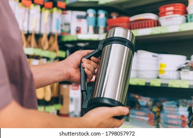 A man in a supermarket holds a thermos in his hands