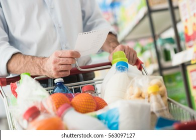 Man at the supermarket shopping with a grocery list and pushing a full cart, lifestyle and retail concept