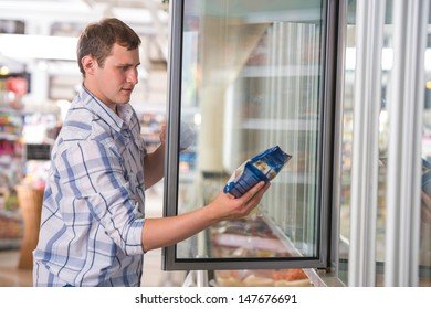 Man in a supermarket standing in front of the freezer looking for his favorite frozen food