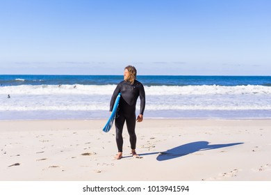 man with surf board on the ocean shore. Surfer in a wet suit. Nazare, Portugal.