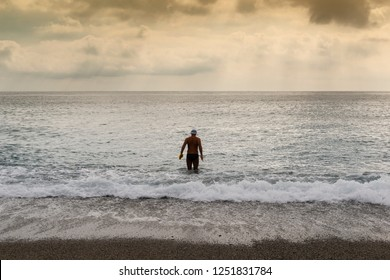 Man in the surf of the shore, he wears cap and goggles and fins in his hands, he is about to dive to swim. The sky is dark and cloudy at sunset, the vast sea is calm