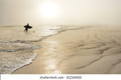 Man  with surfboard on the beautiful foggy beach. Daytona Beach, Florida, USA