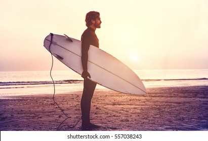 Man surfer carrying his surfboard at sunrise - Hipster male in wetsuit waiting for the high waves on beach - Extreme sport concept - Focus on male silhouette - Matte filter with soft blue vignette