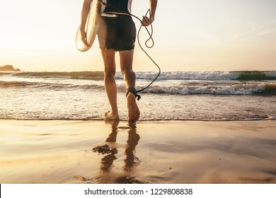 Man surfer run in ocean with surfboard.  Close up legs image
