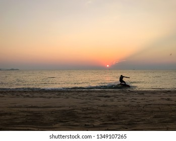 A man is surfing on sea wave at sunset