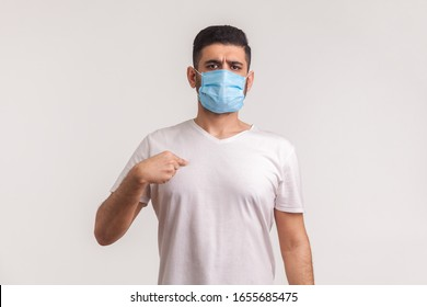 Man in surgical mask pointing himself, wearing protective filter to prevent coronavirus infection, airborne respiratory illness such as flu, 2019-nCoV, ebola. studio shot isolated on white background