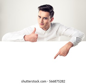 Man surprise showing product .Handsome man  with stylish haircut pointing down . Presenting your product. Isolated on white background. Expressive facial expressions .Young man advertises your product