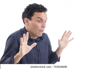 Man is surprised. Hands are up. He's looking down. The person is Caucasian and is wearing blue button-down shirt. Isolated. White background.