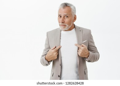 Man surprised and questioned being picked by boss standing unsure over grey wall in elegant formal suit pointing at himself and gazing confused at camera asking uncertain if people talking about him