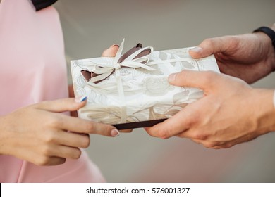 man surprises his girlfriend with present.love, holiday, celebration and family concept