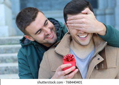 Man surprising his boyfriend with a present