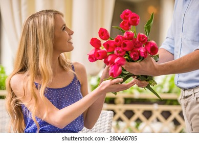 Man surprising his cute girlfriend with flowers on romantic date.