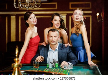 Man surrounded by ladies plays roulette at the casino