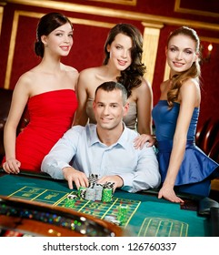 Man surrounded by women gambles roulette at the casino