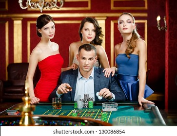 Man surrounded by women gambles roulette at the gambling house
