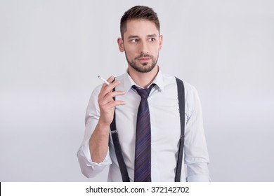Man with suspenders holding a cigarette