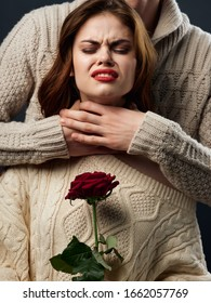 A man in a sweater strangles a woman with bright makeup and a red flower