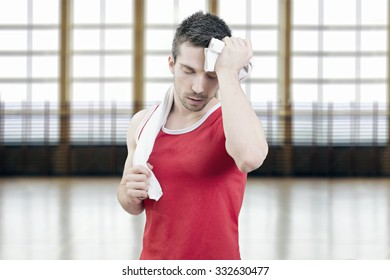 Man sweating after a workout holding a towel