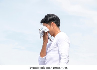 Man is sweating. He is wiping his face with little towel.