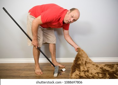 A man sweeping something under the carpet.