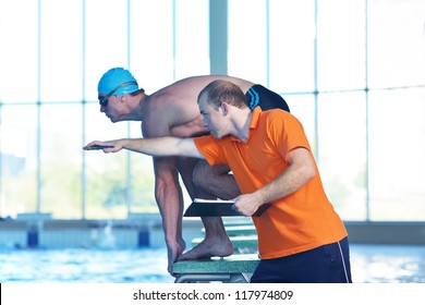 man swimmer practice jump in swimmpin pool with trainer