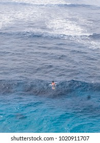 A man swimming alone in the blue ocean.