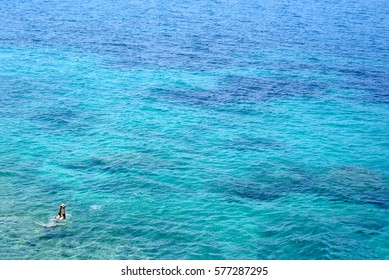 A man swimming in blue and turquoise water of Ionian Sea in Vlora, south of Albania.