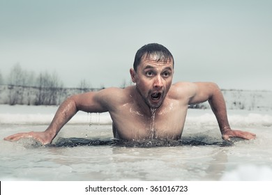 Man swimming in the ice hole with emotional face