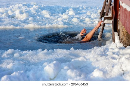 Man swimming in the ice hole at sunny day