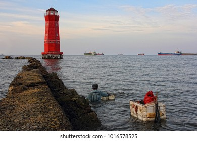 A man is swimming to the lighthouse