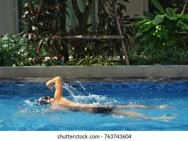 man swimming at pool