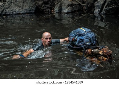 A man is swimming in a river and at the same time supporting a hand-made improvised raft with his backpack. Concept of survival and exploration in the wild. Man vs wild.